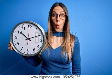 Young blonde woman with blue eyes holding big minute clock over isolated background scared in shock with a surprise face, afraid and excited with fear expression
