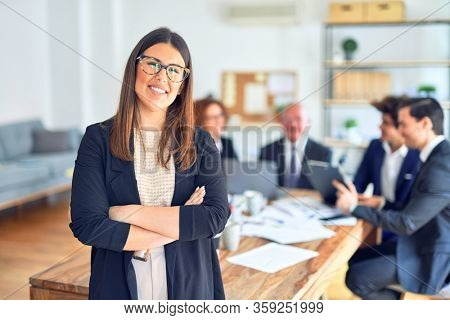 Group of business workers smiling happy and confident working together in a meeting. One of them, standing with smile on face looking at camera at the office.