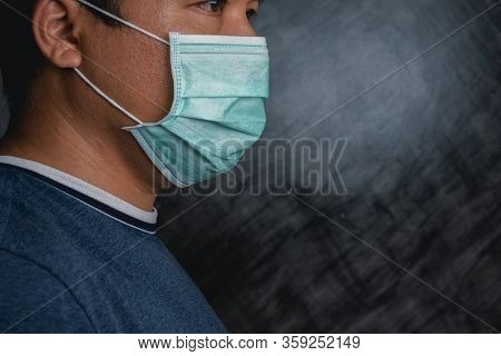 Asian Man Wearing A Surgical Mask To Prevent Face Against Coronavirus With The Dark Background, Conc