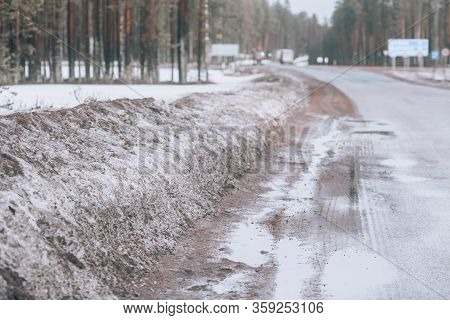Roadside Winter Road. Winter Highway, With Mud, Sand And Snow On The Side Of The Road