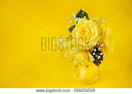 Yellow Rose Flowers Bouquet With Green Leaves In Glas Vase On Bright Yellow Background. Women's Day