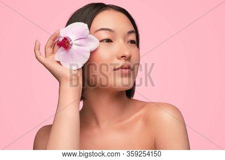 Tender Young Asian Female With Naked Shoulders Keeping Delicate Pink Orchid Flower Near Face And Loo
