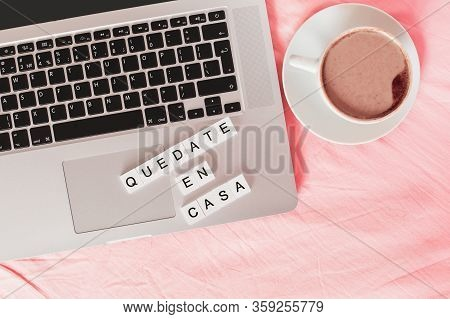 Inscription Stay Home In Spanish - Quedate En Casa, Laptop And Cup With Coffee On The Bed