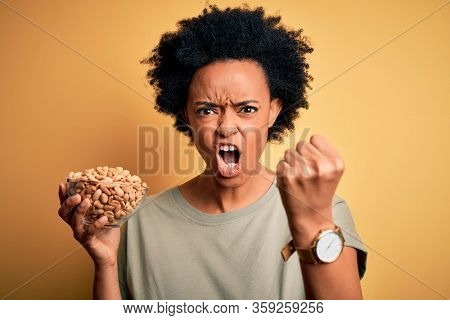 Young African American afro woman with curly hair holding bowl with salty peanuts annoyed and frustrated shouting with anger, crazy and yelling with raised hand, anger concept