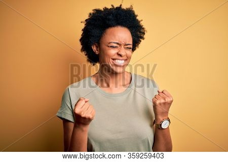 Young beautiful African American afro woman with curly hair wearing casual t-shirt very happy and excited doing winner gesture with arms raised, smiling and screaming for success. Celebration concept.