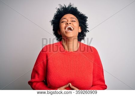 Young beautiful African American afro woman with curly hair wearing red casual sweater smiling and laughing hard out loud because funny crazy joke with hands on body.