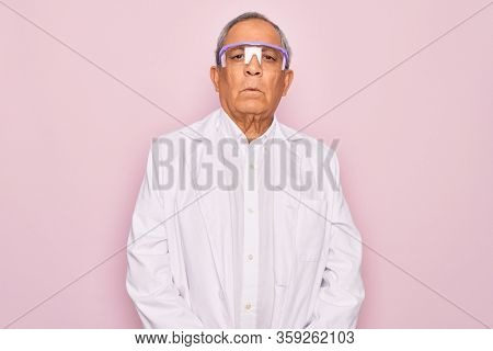 Senior grey-haired scientist man wearing glasses and coat over isolated pink background with serious expression on face. Simple and natural looking at the camera.