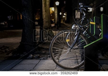 Black Bicycle Parked At Night With City Park Road In The Background. Bicycle Parking Rack. Smart, Au