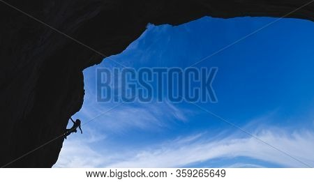 Silhouette Of A Rock Climber Climbing An Arch Shaped Rock, A Woman Overcomes A Difficult Climbing Ro