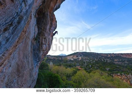 Silhouette Of A Climber Climbing On A Background Of Blue Sky, Strong Woman Overcomes A Difficult Cli