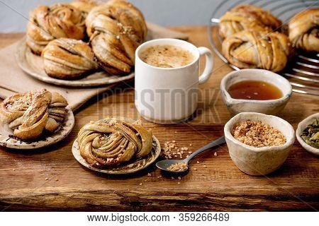 Traditional Swedish Cardamom Sweet Buns Kanelbulle On Cooling Rack, Ingredients In Ceramic Bowl Abov