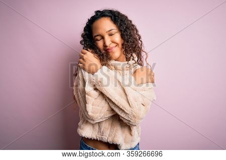 Young beautiful woman with curly hair wearing casual sweater standing over pink background Hugging oneself happy and positive, smiling confident. Self love and self care