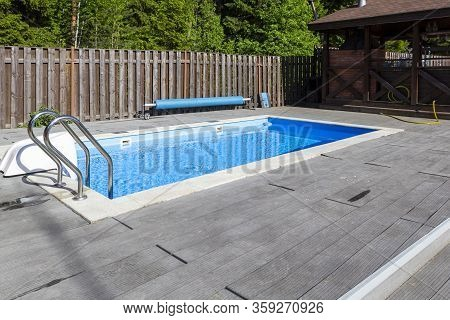 Swimming Pool, Patio Area And Barbecue Gazebo In Backyard Of Country House