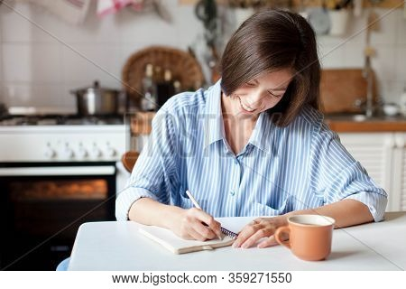 Young Woman Writting Notes In Paper Notebook. Happy Girl Sitting At Table With Cup Of Coffee In Cozy