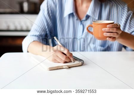 Young Woman Writing Notes In Paper Notebook. Happy Girl Sitting At Table With Cup Of Coffee In Cozy
