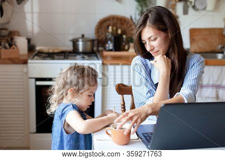 Working Mom Works From Home Office With Kid. Woman And Cute Child Using Laptop. Freelancer Workplace