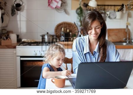Working Mom Works From Home Office With Kid. Happy Mother And Daughter. Woman And Cute Child Using L
