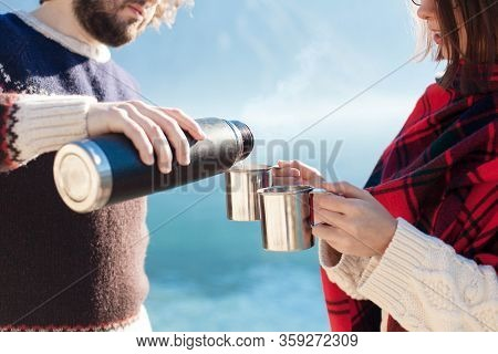 Couple Of Travelers Drink Coffee. Winter Picnic At Sea Beach. Man Pouring Tea From Thermos. Woman Ho