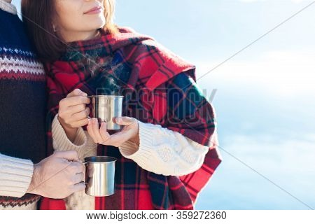 Couple In Love Drink Coffee At Winter Sea Beach. Travelers Hold Camping Cups With Steamy Tea. Young
