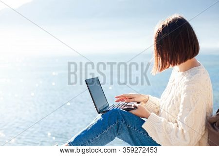 Young Woman Working At Sea Beach. Girl Freelancer Using Laptop And The Internet In Outdoor Office In