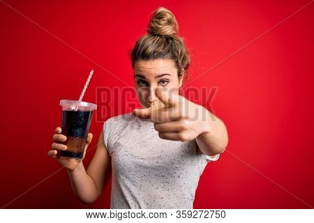 Beautiful blonde woman drinking cola fizzy beverage to refreshment over red background pointing with finger to the camera and to you, hand sign, positive and confident gesture from the front