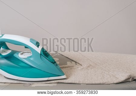 Iron Disinfection Of Clothes. The Iron Is On The Ironing Board. Ironing Process.