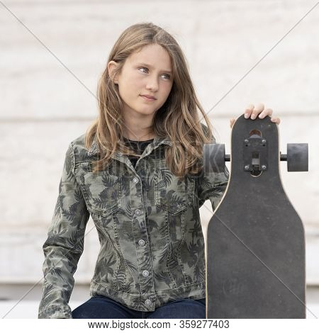 Portrait Of Young Girl With Skateboard, France, Europe