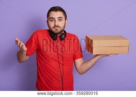 Front View Of Delivery Man With Carton Box In Hands, Having Headphones Around Neck, Making Helpless