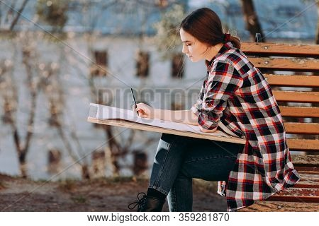 Young Woman Artist Draws A Picture While Sitting On A Bench. Painter Artist Holds A Wooden Tablet Fo
