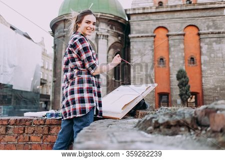 Pretty Young Woman Artist Paints Old Architecture In The City. Girl Spends Leisure Drawing Pictures