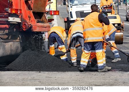 The Team Of Road Workers Updates Part Of The Road With Fresh Asphalt And Levels It With Shovels To E