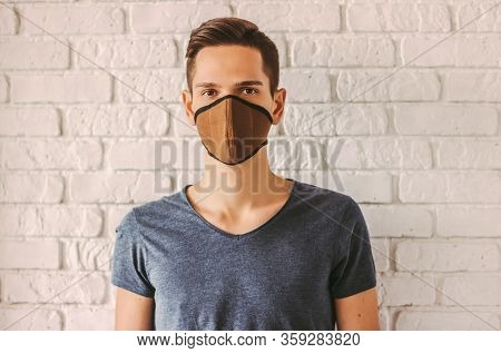 Young Man In Protective Face Mask As Preventive Measure From Chinese Coronavirus Covid-19. Hipster M