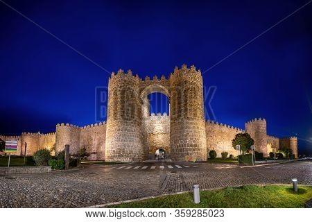 Avila, Spain. View Of Historic City Gate Puerta De San Vicente At Dusk