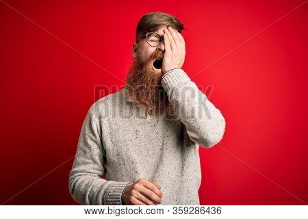 Handsome Irish redhead man with beard wearing casual sweater and glasses over red background Yawning tired covering half face, eye and mouth with hand. Face hurts in pain.