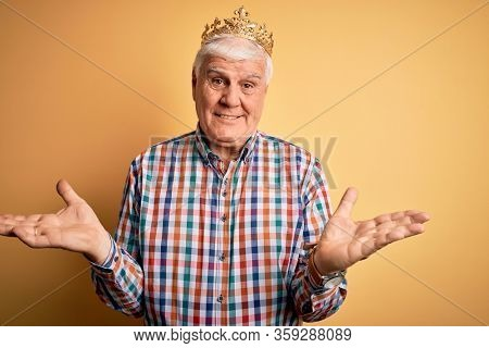 Senior handsome hoary man wearing golden crown of king over isolated yellow background clueless and confused expression with arms and hands raised. Doubt concept.