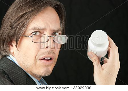 Casual Businessman Wearing Reading Glasses Frustrated Trying To Read Pill Bottle Label