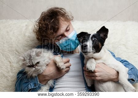 A Man With His Pet Is Sitting On A Sofa At Home. Quarantine Coronavirus.