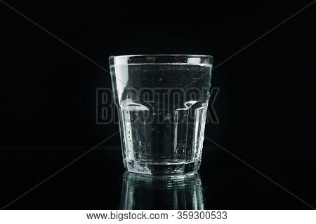 Purified Fresh Water In Glass On Mirror Background