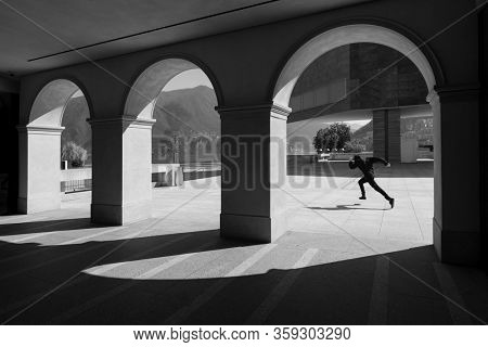 Silhouette of a boy running, he seems to be running away from something. black and white photography with very accentuated shadows. They can be seen in the foreground between beautiful arches