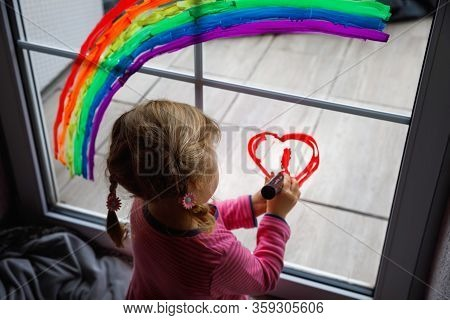 Adoralbe Little Toddler Girl With Rainbow Painted With Colorful Window Color During Pandemic Coronav