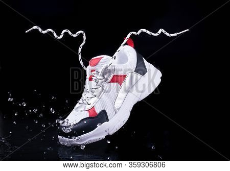 Sports Sneakers On A Black Isolated Background In Splashes Of Water, Youth Sports Shoes, Floating La