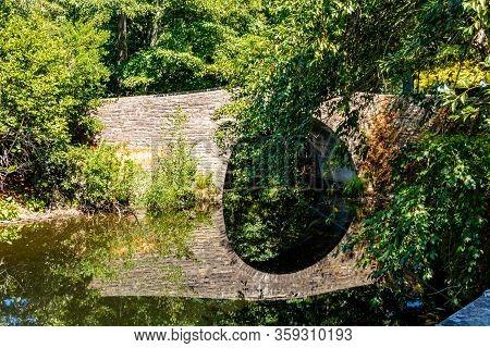Stone Bridge Refelcted In A Pond. Hamilton Gardens, Hamilton, New Zealand