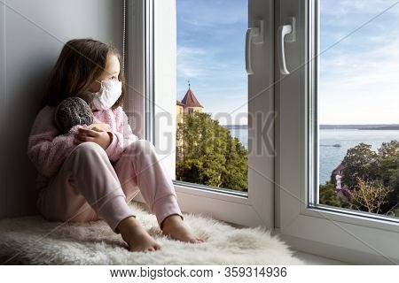 Covid-19 Coronavirus Concept, Little Girl In Medical Mask Looks Out Window In House. Sad Kid Is In R