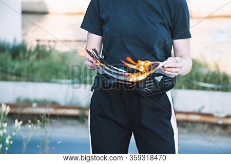Hot Newspaper. Young Girl Holds A Burning Newspaper In Her Hands. Concept Of A Girl With A Burning N