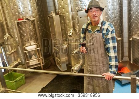 Winemaker or wine master with a glass of red wine while making wine