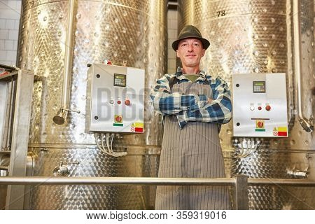Confident winemaker in front of a fermentation tank with his arms crossed