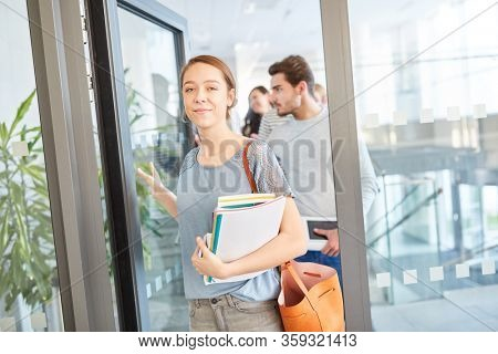 Woman as freshmen student in the uni holds her books