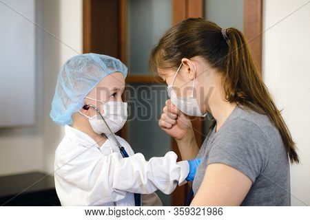 Small Boy Playing Doctor And Patient With His Mother Wearing A Stethoscope