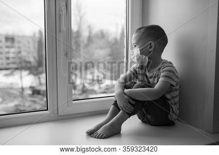 Sad Little Boy In Medicine Mask Sitting Near Window And Looking Outside, Quarantine At Home, Virus P