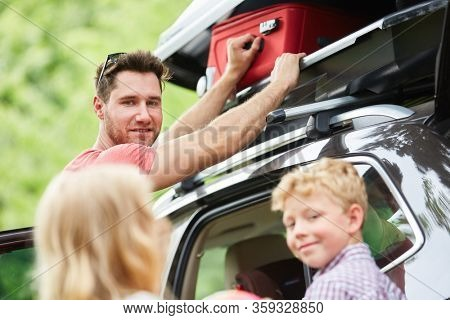Family stows luggage in the roof box on the car before leaving for vacation